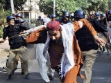 Police chase activists of Jamaat-e-Sunnah and supporters of convicted killer Malik Mumtaz Hussain Qadri during a protest in Lahore on October 3, 2011. PHOTO: AFP