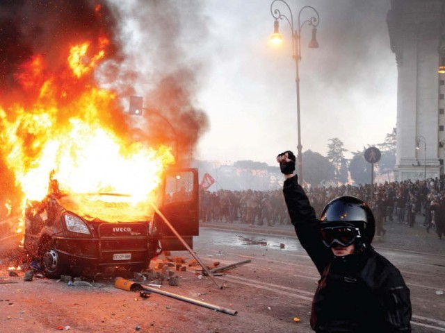 A demonstrator celebrates as a police vehicle burns during a demonstration of the 'Indignant' group in Rome. The protesters have now spread worldwide. PHOTO: REUTERS