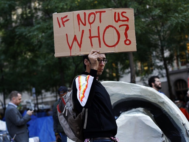 An Occupy Wall Street campaign demonstrator holds a sign in Zuccotti Park, near Wall Street in New York October 17, 2011. PHOTO: Reuters
