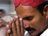 A man bows his head in prayer while the fakir sits near a staircase and waits for people to walk by when they light the diyas.