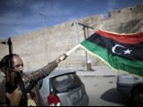 A Libyan fighter waves a National Transitional Council (NTC) flag as he  celebrates in the streets of  Tripoli  following news of Moamer Kahdafi's capture on October 20, 2011. PHOTO: AFP