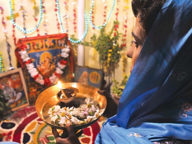 Amid the festivities, a woman prays while holding an oil lamp. PHOTO: MUHAMMAD JAVAID