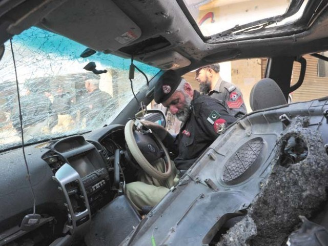 Police officials inspect wreckage of the vehicle following the suicide bomb attack. PHOTO: AFP