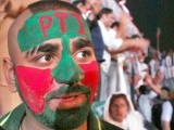 PTI supporter has his face painted in the colors of the party flag in Lahore at the jalsa on OCtober 30, 2011. PHOTO : NNI