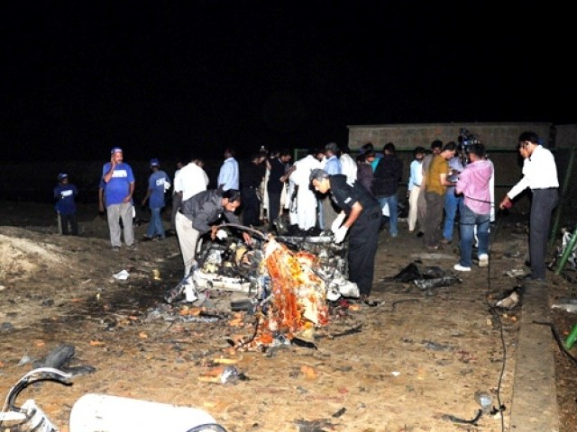 Pakistani security officials scan the wreckage of a vehicle after three suicide bombers blew themselves up in their car when intercepted by police in Karachi on November 16, 2011. PHOTO: AFP