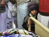 A boy stands with colleagues and family members of a policeman, who was injured by an explosion, at his bed-side after he was brought for treatment to a hospital in Mardan located in northwest Pakistan November 22, 2011. PHOTO: REUTERS