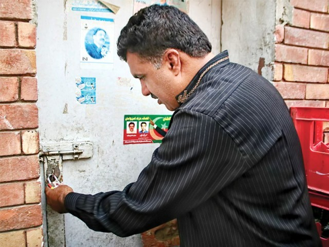 Pakistan Tehreek-i-Insaf's deputy information secretary tries to break open the lock using a brick. PHOTO: NNI