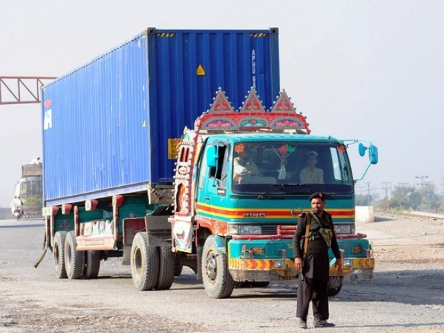 Security personnel watch a truck carrying supplies for NATO forces in Afghanistan return from the Torkham border crossing after Pakistani authorities suspended NATO supplies on November 26, 2011. PHOTO: AFP