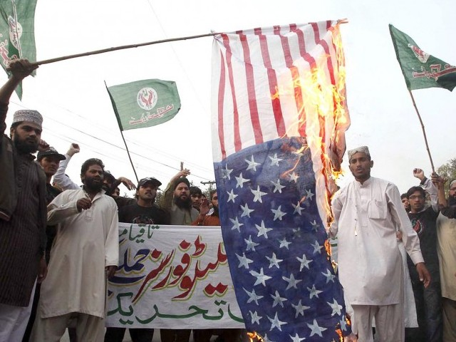 Protestors burning a US flag, protesting againt the Nato attack on the checkpost on Saturday. PHOTO: INP