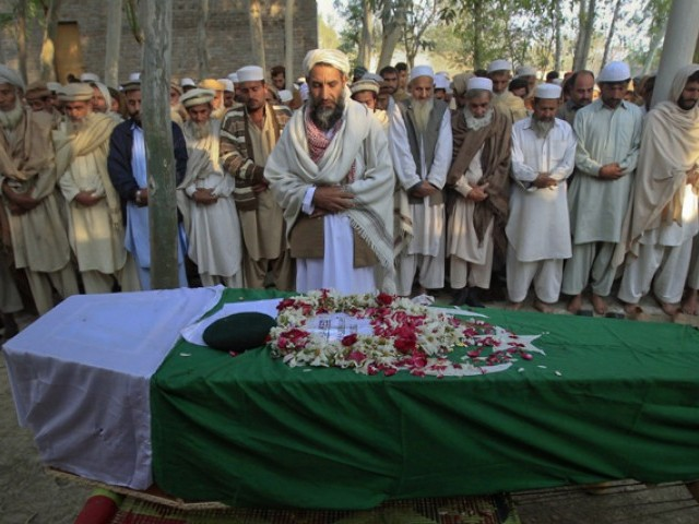 Relatives and residents pray near the flag-draped coffin of solider Najeebullah, who was killed in a Nato cross-border attack one day earlier, during his funeral in his hometown Charsadda in northwest Pakistan November 27, 2011.  PHOTO: REUTERS/FILE