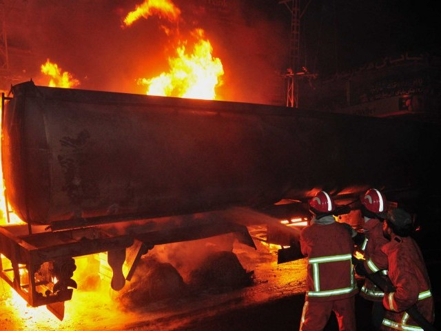 Firefighters extinguish burning NATO supply oil tankers and goods trucks at a terminal following an attack by gunmen in Quetta on December 8, 2011.
