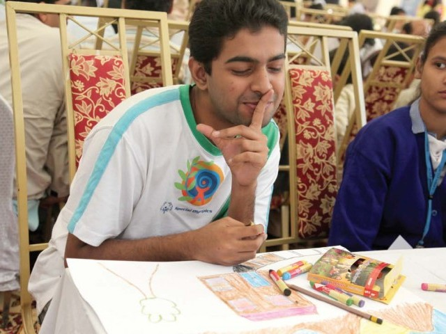 A participant asks his competitor to be quiet so that he can continue working on his art piece. Special children from different schools took part in an art compeititon organised by the Network of Organisations Working for People with Disabilities Pakistan. PHOTO: NEFER SEHGAL/EXPRESS