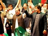 Imran Khan (R) joins hands with his party leader Javed Hashmi (C)during a public meeting gathering over 100,000 people in Karachi on December 25, 2011. PHOTO: AFP