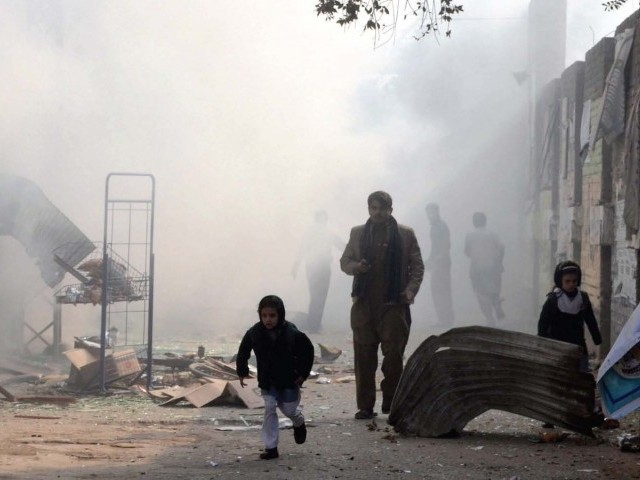 School girls and pedestrians move away from the site of a bomb blast in Peshawar. PHOTO: AFP