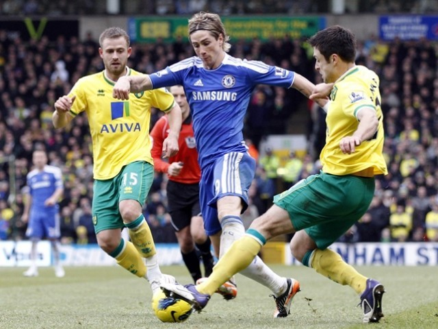 Norwich City's David Fox (L) and Russell Martin (R) challenge Chelsea's Fernando Torres during their English Premier League soccer match at Carrow Road in Norwich, eastern England, January 21, 2012. PHOTO: REUTERS