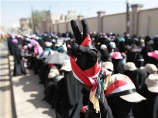 A woman flashes a victory sign during a march in solidarity with the people of Syria in Sanaa. PHOTO: REUTERS