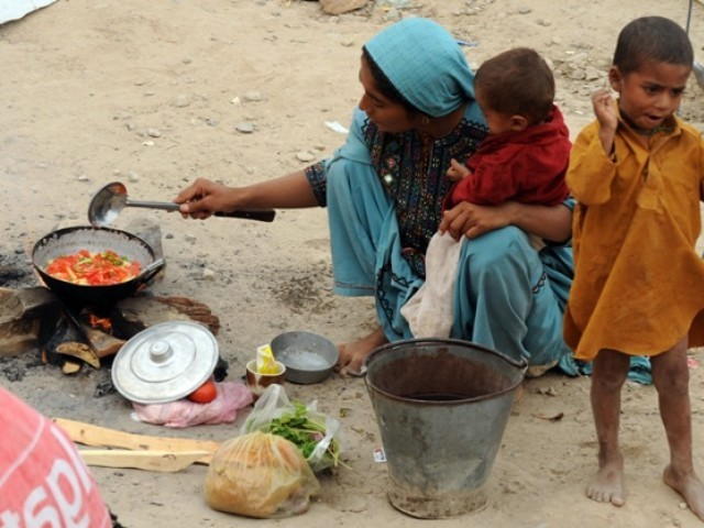 In this photograph taken on August 25, 2010, a Pakistani woman displaced by floods holds her baby as she prepares food. PHOTO: FILE/AFP