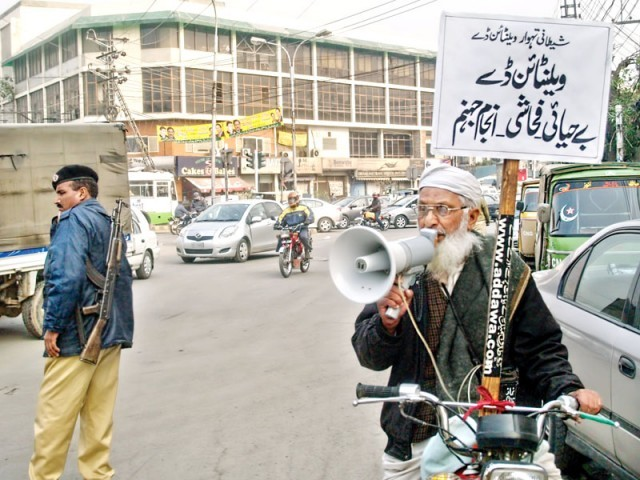 A man bikes around Davis Road raising his voice against the 'evils' of Valentine's Day. PHOTO: ABID NAWAZ/EXPRESS