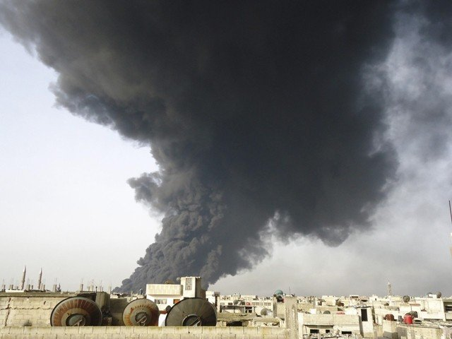 Black smoke is seen from Homs refinery on February 15, 2012. PHOTO: REUTERS