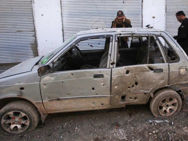 Policemen survey a damaged vehicle at the site of a bomb blast in Jamrud market, about 25 km west of Peshawar, February 15, 2012. PHOTO: REUTERS