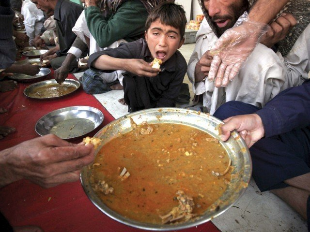 A boy eats at a charity food distribution stall. PHOTOS: REUTERS