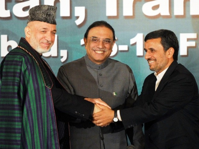 Afghanistan's President Hamid Karzai (L), Pakistan's President Asif Ali Zardari (C) and Iranian counterpart Mahmoud Ahmadinejad (R) join hands after a joint press conference at the Presidential Palace in Islamabad on February 17, 2012. PHOTO: AFP