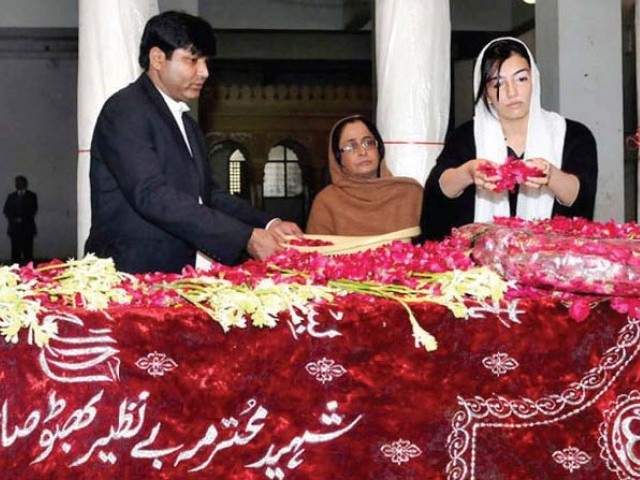 Aseefa Bhutto-Zardari showers her mother's grave with rose petals in this file photo from January 1, 2012. She is Benazir Bhutto's youngest child. PHOTO: FILE