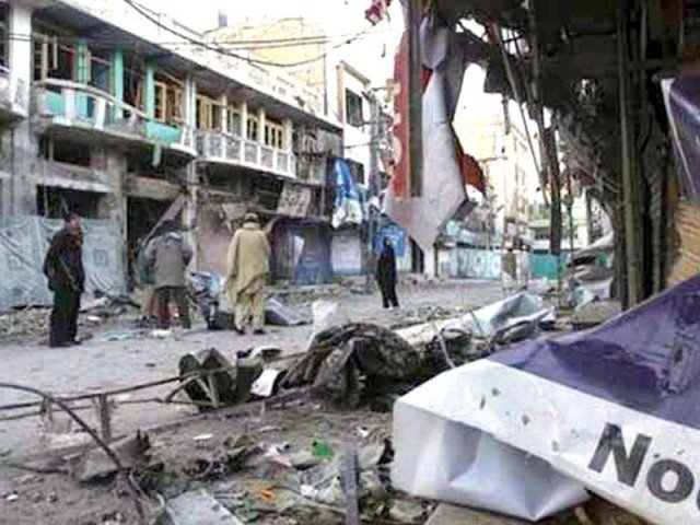 Residents walk past the blast site in Parachinar. PHOTO: FILE