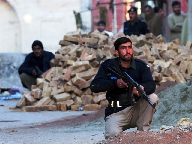 Policemen take position during a militant attack on a police station in Peshawar on February 24, 2012. PHOTO: AFP