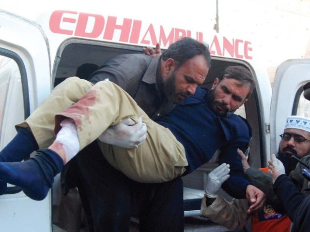 An injured policeman is helped off an ambulance outside a hospital in Peshawar following the bomb blast in Nowshera.  PHOTO: AFP