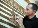 Cuban tobacco sculptor Janio Nunez adjusts one of his pieces made out of tobacco leaves. PHOTO: AFP