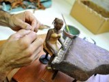 Cuban tobacco sculptor Janio Nunez works on his piano player sculpture made out of tobacco leaves. PHOTO: AFP