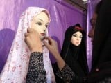 An Iranian woman adjusts a chador on a mannequin at the Islamic fashion exhibit in central Tehran on March 1, 2012. PHOTO: AFP
