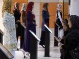 Iranian women walk past mannequins covered with Islamic clothing designed by Iranian designers during an Islamic fashion exhibition in central Tehran March 1, 2012.
