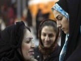 An Iranian woman tries on a scarf during an Islamic fashion exhibition in central Tehran March 1, 2012.