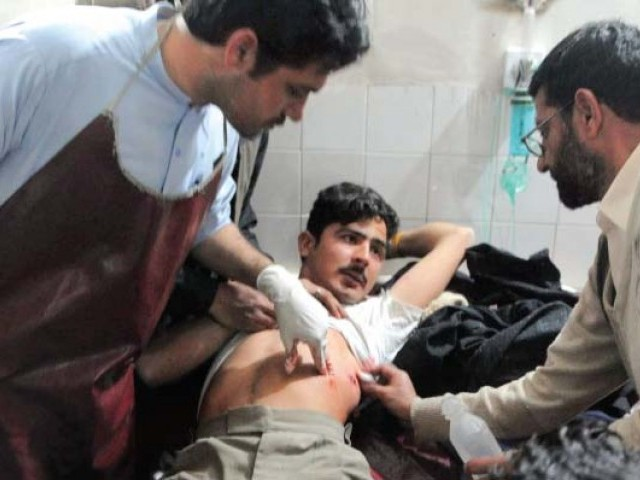 Paramedics tend to a wounded victim of the suicide attack at a hospital in Peshawar. PHOTO: AFP