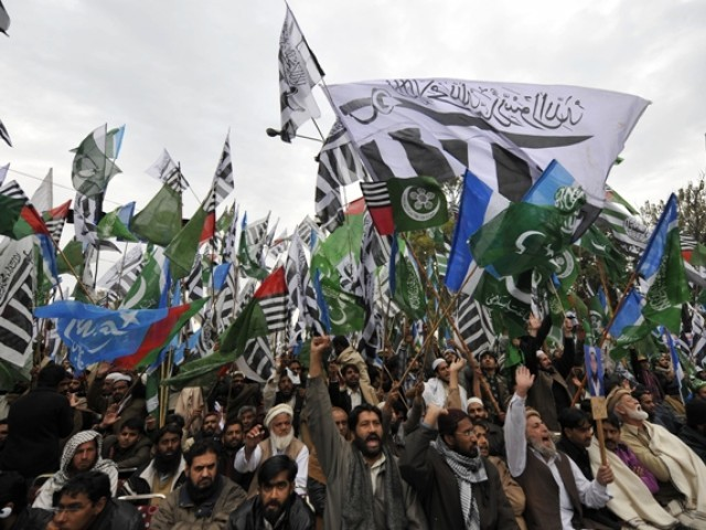 Activists of members of Difa-e-Pakistan Council hold flags as they shout anti-US slogans at the rally in Islamabad on February 20, 2012. PHOTO: AFP/FILE