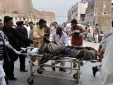 Relatives and volunteers shift a body from a hospital after a suicide attack in Peshawar on March 11, 2012. PHOTO: AFP