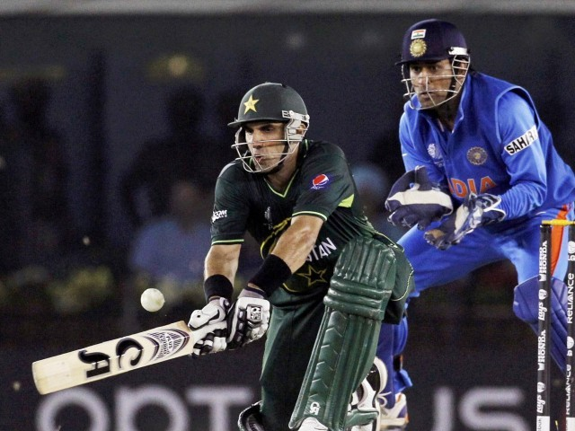 Pakistan's Misbah-ul-Haq (L) plays a shot as India's captain and wicketkeeper Mahendra Singh Dhoni watches during their ICC Cricket World Cup 2011 semi-final match in Mohali March 30, 2011. PHOTO: REUTERS