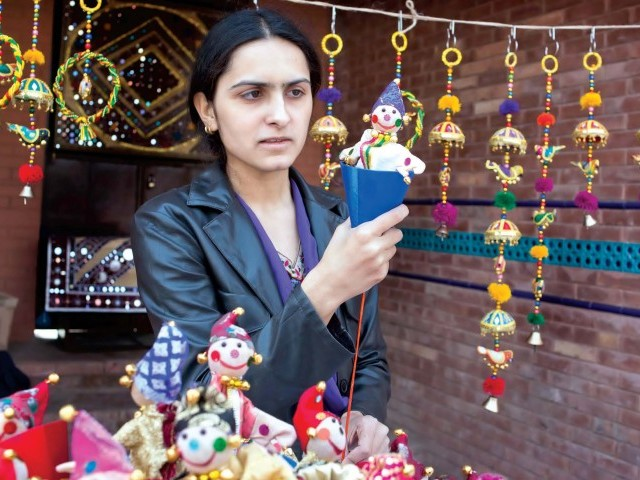 Hard at work at her stall in the Lok Virsa festival, Ambreen Fatima hopes for renewed sales in an environment not friendly to cultivation of the arts. PHOTO: MYRA IQBAL