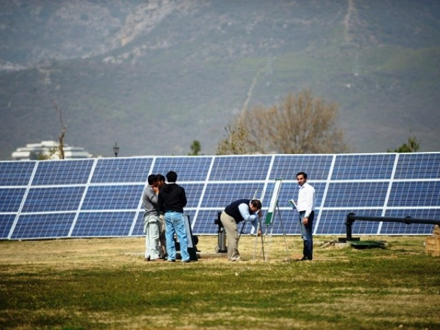 Company employees arrange solar panels for a marketing demonstration in a park in Islamabad on March 10, 2012. PHOTO: AFP