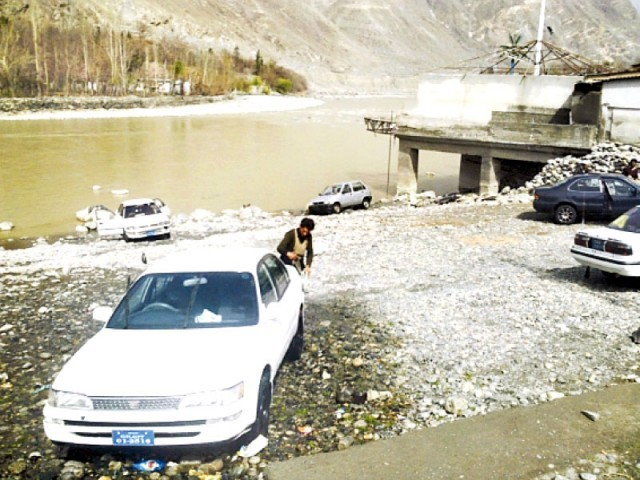 Locals wash cloths (left) and cars (right) on the banks of Gilgit River, polluting the water and endangering the river's biodiversity. PHOTO: SHABBIR MIR/EXPRESS