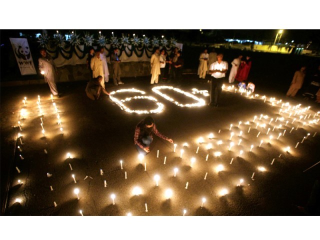 Participants light candles at a ceremony organised in front of National Assembly building on Saturday. PHOTO: MUHAMMAD JAVAID