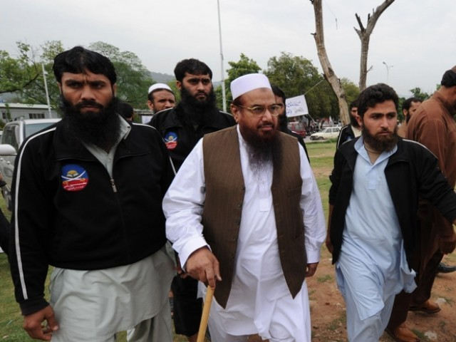 This photograph taken on April 11, 2011 shows chief of the Jamaatud Dawa Hafiz Mohammad Saeed (C) arriving to attend funeral prayers in absentia for Indian Kashmir's Muslim cleric Moulvi Shoukat Ahmad Shah. PHOTO: AFP