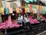 Shopkeepers wait for customers at their stalls selling cloths with religious inscriptions and flower petals outside the shrine of Sufi saint Khwaja Moinuddin Chishti. PHOTO: REUTERS