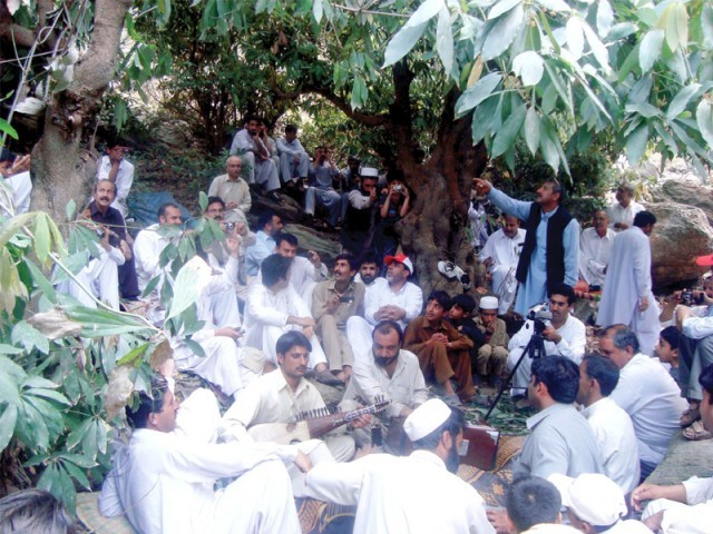 A man plays a traditional musical instrument, as others sit around him to welcome spring. PHOTO: FAZAL KHALIQ / EXPRESS