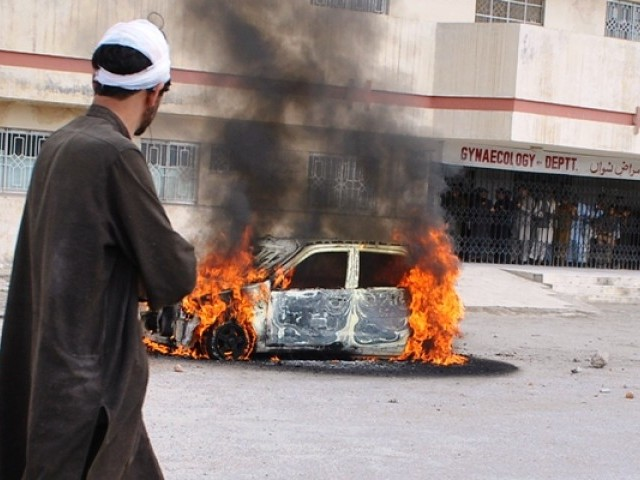 An injured man walks past a burning car after in Quetta on April 14, 2012. PHOTO: AFP