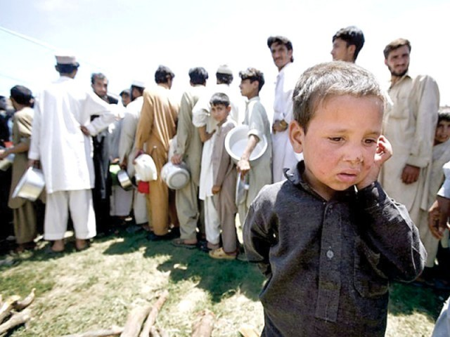 A young boy walks past IDPs queuing up for food rations. 2000 Mehsud IDPs to start returning home from April 25 PHOTO: FILE