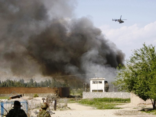 An Afghan National Army soldier keeps watch near the Provincial Reconstruction Team (PRT) as a NATO helicopter flies over the site of an attack in Jalalabad province April 15, 2012. PHOTO: REUTERS/FILE