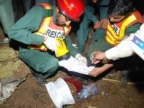 Rescue workers peer over a document as they search for survivors among the wreckage of Bhoja Air B4-213. PHOTO: MUHAMMAD JAVAID/EXPRESS TRIBUNE